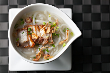 top down: Closeup top down view of Thai style crispy pork rice noodle soup in a bowl with copy space.