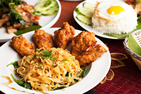 Thai style fried siracha chicken wings on a round white plate with egg noodles and spinach. photo