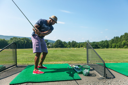 casual attire: Athletic golfer swinging at the driving range dressed in casual attire. Stock Photo