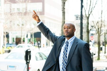 raises: An African American business man raises his hand to hail a cab in the city.