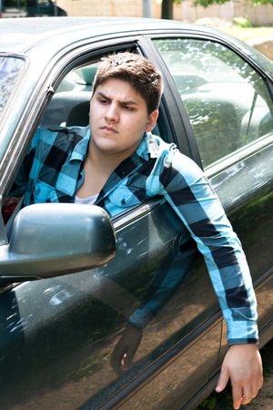 An irritated young man driving a vehicle with his head and arm hanging out of the window. photo