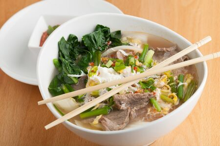 thai noodle soup: Closeup of some Thai pho style soup with beef and clear rice noodles. Stock Photo