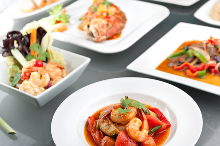 thai arts: Variety of Thai style whole fish red snapper sweet and sour shrimp gyoza dumplings sesame breads seafood salad and other spicy Thai dishes. Stock Photo