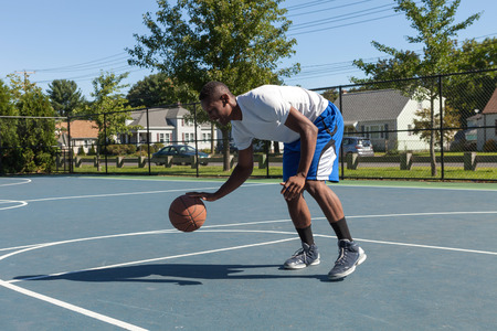 moves: A sweaty young basketball player dribbling down the court demonstrating his ball handling skills. Stock Photo