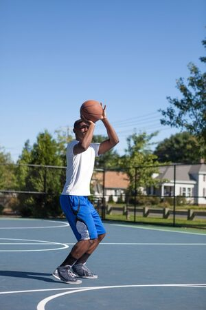 baller: Basketball player shooting the ball at the basket on an outdoor court.