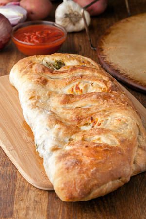 stromboli: Homemade stromboli or stuffed bread with broccoli potatoes garlic onions and mozzarella cheese along with a side of marinara dipping sauce. Stock Photo