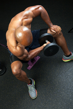 jacked: Toned and ripped lean muscle fitness man lifting weights on a curling bar. Stock Photo