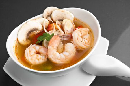 king of thailand: Thai shrimp soup bowl close up with mushrooms and vegetables. Stock Photo