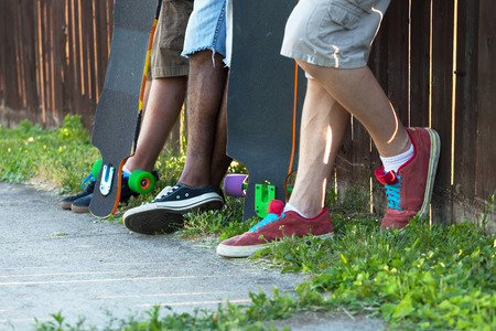 boarders: Longboarders feet standing along an urban fence line with their skateboards. Shallow depth of field.