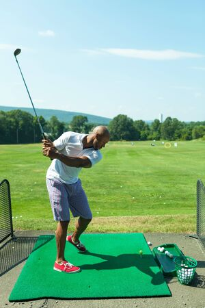 driving range: Athletic golfer swinging at the driving range dressed in casual attire. Stock Photo