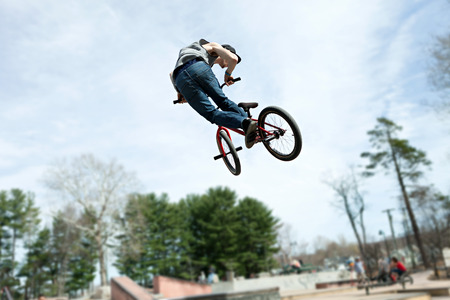 bmx bike: BMX rider athlete spinning his entire bike mid air.  Slight motion blue due to movement.