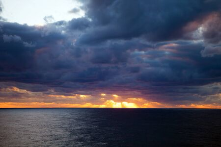 clouded: Sunset through the clouds over the Atlantic Ocean.