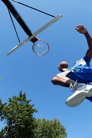 dunk: Young basketball player driving to the hoop for a high flying slam dunk. Shallow depth of field.