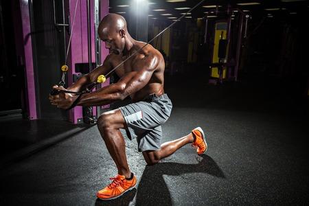 근육 바디 빌더는 케이블 와이어 시스템에 가슴 비행 연습을 하 고 체육관에서 밖으로 작동합니다. 스톡 콘텐츠