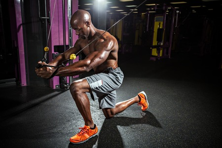 musculoso: Constructor del cuerpo muscular que se resuelve en el gimnasio haciendo ejercicios de mosca pecho en la máquina de cable de alambre.