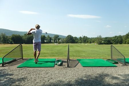Athletic golfer swinging at the driving range dressed in casual attire. Stockfoto