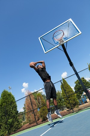 baller: Young basketball player driving to the hoop for a high flying slam dunk. Shallow depth of field.