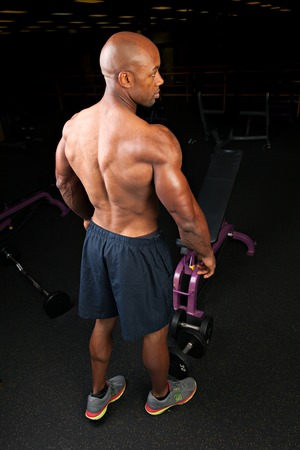 jacked: Toned and ripped lean muscle fitness man showing his back and triceps. Stock Photo
