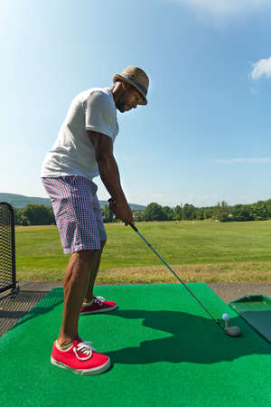 casual attire: Athletic golfer teeing up at the driving range dressed in casual attire.