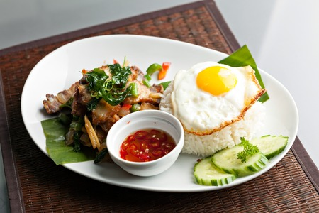sauce dish: Traditional Thai dish crispy pork with a fried egg atop the jasmine rice served with chili sauce. Stock Photo