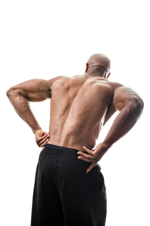 back ache: Portrait of a muscle fitness man reaching for his lower back in pain Stock Photo
