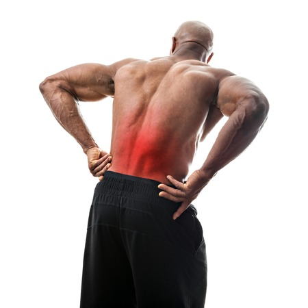 Fit man or athlete reaching for his lower back in pain with the painful area highlighted in red. Stock Photo