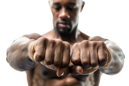 jacked: Muscular man of African descent isolated over a white background showing a closeup of his fists and knuckles.  Shallow depth of field.