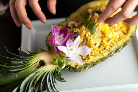 pineapple: Freshly prepared pineapple fried rice served inside of a pineapple carved like a bowl. Food stylish is arranging garnish. Stock Photo
