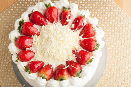 shortcake: Top view of an entire strawberry shortcake with white chocolate shavings.  Shallow depth of field. Stock Photo