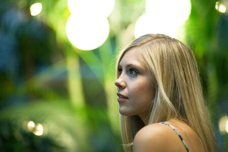 Contemplative young blonde woman under warm tungsten lighting. Shallow depth of field.