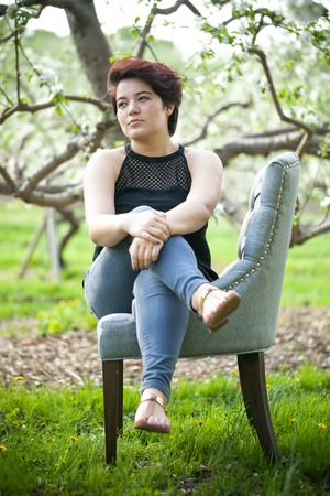 highlighted hair: Attractive brunette woman under soft natural lighting near some apple trees. Shallow depth of field.