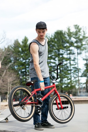 tanktop: BMX bike rider with his bicycle at the skate park. Shallow depth of field. Stock Photo