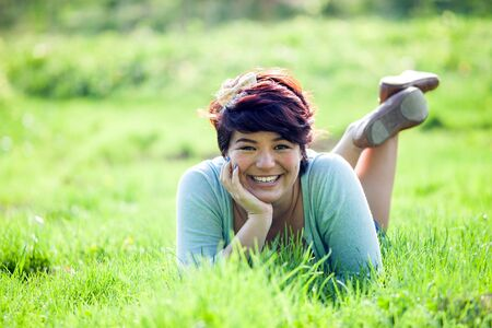 highlighted hair: Smiling teenage girl laying in a green grassy field. Shallow depth of field.