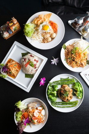 Variety of authentic Thai cuisine and stir fry dishes.  Shallow depth of field. Imagens