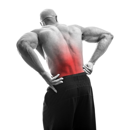 lower back pain: Portrait of a muscle fitness man reaching for his lower back in pain Stock Photo