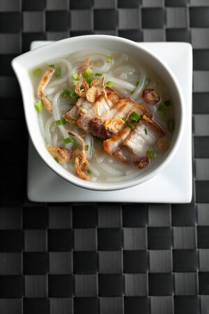 chinese noodle: Close up top down view of Thai style crispy pork rice noodle soup in a bowl with copy space.
