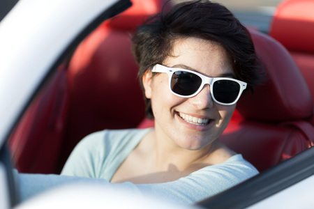 drive car: Portrait of smiling woman wearing sunglasses in a convertible sports car with red leather interior. Stock Photo