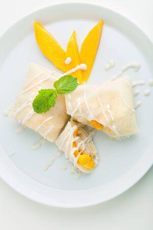 Thaise stijl tropische dessert pannenkoeken gevuld met verse mango en sticky rijst. Top-down bovenaanzicht.