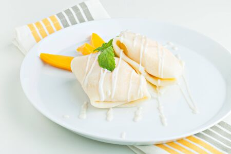 thai dessert: Thai style tropical dessert crepes filled with fresh mango and sticky rice. Shallow depth of field. Stock Photo