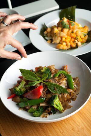 Food stylist bruidegoms een gerecht door het toevoegen van zoete basilicum Garneer met de traditionele Thaise schotel Pad Kee Mao dronken noodle. Stockfoto