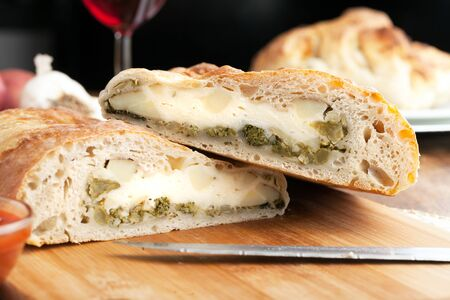 Zelfgemaakte Stromboli of gevuld brood met broccoli aardappelen knoflook uien en mozzarella kaas samen met een kant van Marinara dipsaus.