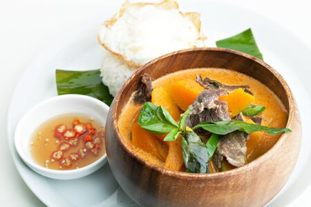 Pumpkin red curry with beef and basil. Archivio Fotografico
