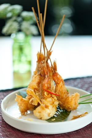Tempura jumbo shrimp skewers on a white plate standing up vertically. Stock Photo