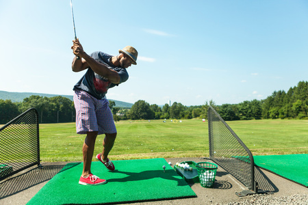 Athletic golfer swinging at the driving range dressed in casual attire. Standard-Bild