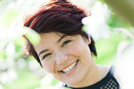 Glimlachend aantrekkelijke brunette vrouw onder zachte natuurlijke verlichting. Ondiepe scherptediepte.