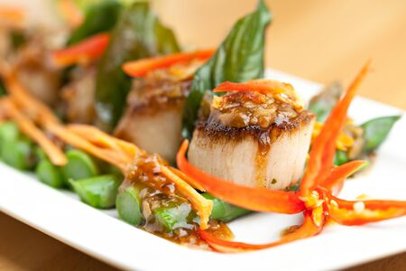 Spicy thai scallops on a bed of asparagus spears. Standard-Bild