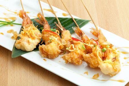 jumbo shrimp: Tempura jumbo shrimp skewers on a white plate.