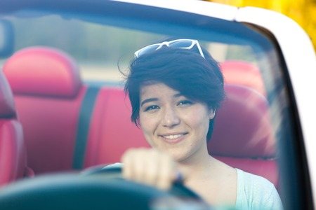 Portrait of smiling woman in a convertible sports car with red leather interior. Shallow depth of field.