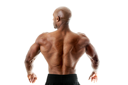 Toned and ripped lean muscle fitness man standing in front of a white background. Shallow depth of field. Stock Photo