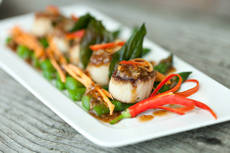 Spicy thai scallops on a bed of asparagus spears. Stock Photo